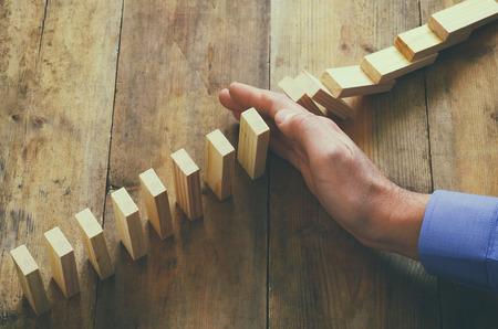 una mano maschile stoping l'effetto domino. immagine retrò stile esecutivo e il concetto di controllo del rischio