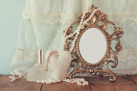 style woman: Antique blank victorian style frame, perfume bottle and white pearls on wooden table. retro filtered and toned. template, ready to put photography