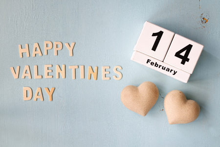 february 14th: February 14th wooden vintage calendar and the words happy valentines day made with block wooden letters next to couple of hearts on light blue wooden background