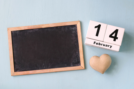 february 14th: February 14th wooden vintage calendar and wooden heart next to blackboard on wooden light blue background. valentines day celebration concept. vintage filtered and toned