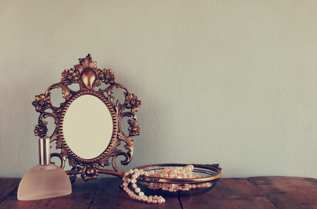 Antique blank victorian style frame, perfume bottle and white pearls on wooden table. retro filtered and toned. template, ready to put photography