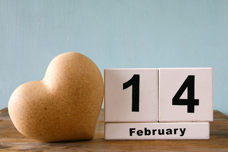 14th: February 14th wooden vintage calendar next to heart on wooden table. vintage filtered