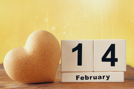 february 14th: February 14th wooden vintage calendar next to heart on wooden table. glitter background. vintage filtered