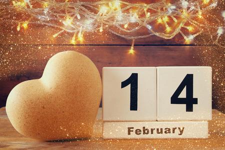 imagen: 14ª calendario de febrero de la vendimia de madera junto a corazón en la mesa de madera. vendimia filtrada
