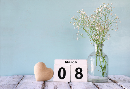 wooden March 8 calendar, next to heart and white flowers on old rustic table. selective focus