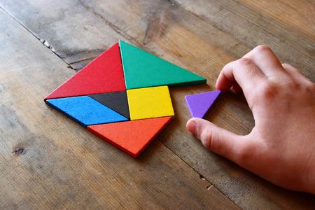 la mano del hombre la celebración de una pieza que falta en un rompecabezas tangram cuadrado, sobre la mesa de madera. Foto de archivo