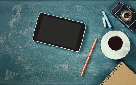 notebook design: top view image of tablet, cup of coffee and photo camera over blackboard background Stock Photo