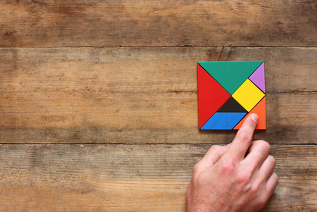 kid's hand holding a missing piece in a square tangram puzzle, over wooden table.