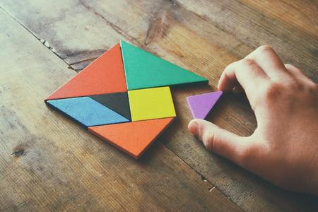 kid's hand met een ontbrekende stukje in een vierkant tangram puzzel, over houten tafel. Stockfoto