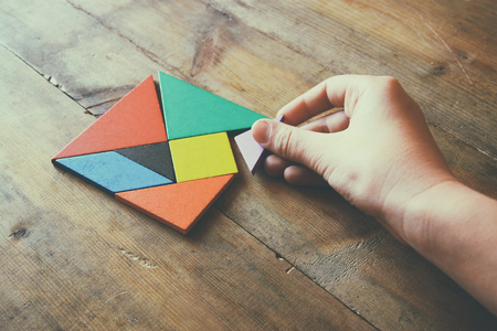 color tangram: kids hand holding a missing piece in a square tangram puzzle, over wooden table. Stock Photo