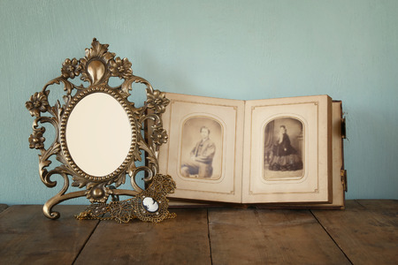 old photograph: Antique blank victorian style frame and old open photograph album with vintage necklace on wooden table. retro filtered image. template, ready to put photography Stock Photo