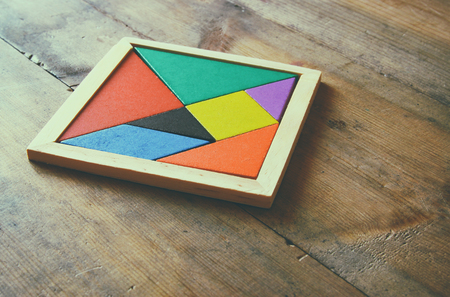 a square tangram puzzle, over wooden table.