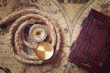 brujula: image of old compass and rope next to old book on vintage map Foto de archivo