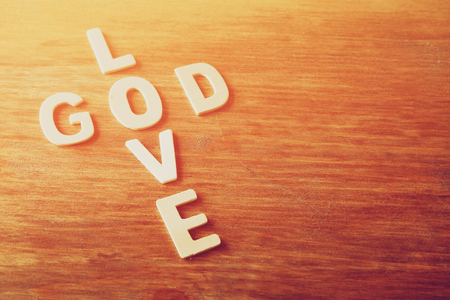 selective focus photo of The words love is god made with block wooden letters on wooden background. religion concept Stock Photo