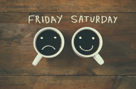 coffee cup with sad and happy faces next to friday saturday phrase background. vintage filtered. happy weekend concept