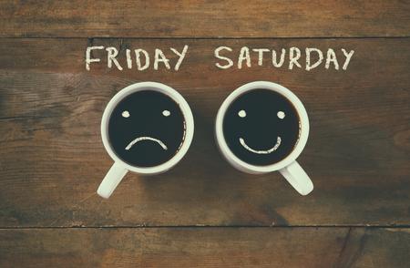 """caras tristes: taza de café con caras tristes y felices al lado de """"Viernes Sábado"""" fondo frase. la vendimia se filtró. concepto feliz fin de semana"""