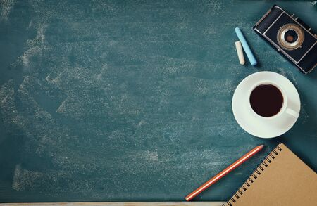 chalk board: top view image of cup of coffee, notebook and vintage camera over blackboard background