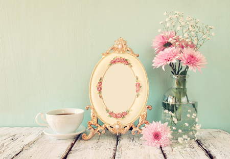 tea table: vintage perfume bottle next to pink and white flowers and antique frame on wooden table. vintage filtered. Stock Photo