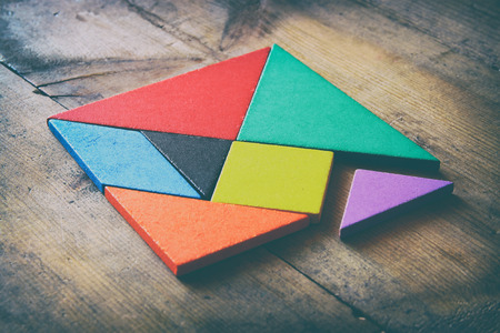 a missing piece in a square tangram puzzle, over wooden table. Foto de archivo