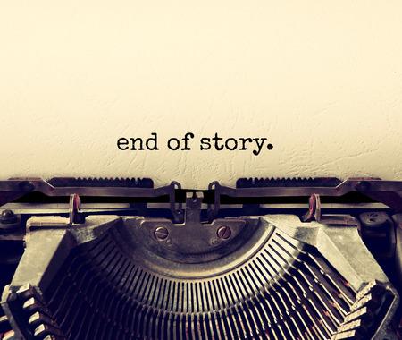 imagen: de cerca la imagen de la máquina de escribir con la hoja de papel y la frase: fin de la historia. copia espacio para el texto. Terto filtrada Foto de archivo