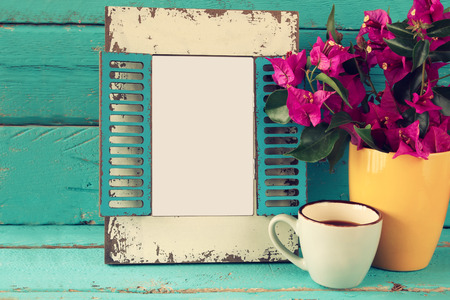 table: vintage blank frame, cup of coffee next to beautiful purple mediterranean summer flowers.  template, ready to put photography
