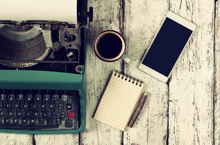 ヴィンテージ タイプライター、空白のノートブック、一杯のコーヒーと木製のテーブルでのスマート フォンのレトロなフィルター処理されたイメージ