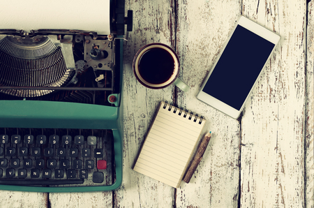 retro filtered image of vintage typewriter, blank notebook, cup of coffee and smartphone on wooden table Banco de Imagens