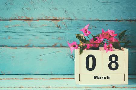 kalendarium: Drewniana 08 marca kalendarza, obok purpurowe kwiaty na starym niebieskim tamtejsze tabeli. selektywnej ostrości. rocznik filtrowane