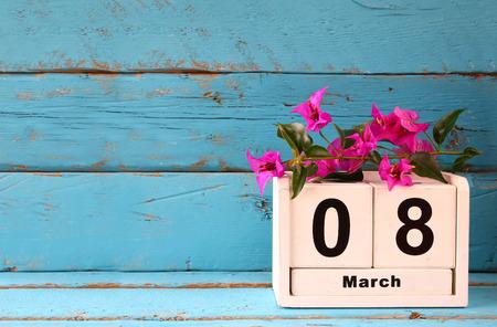 Holz 8. März Kalender, neben lila Blumen auf alten blauen rustikalen Tisch. selektiven Fokus. Jahrgang gefiltert Standard-Bild