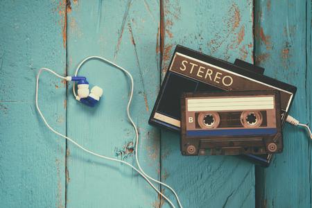 Cassette and old tape player over wooden background. retro filter Reklamní fotografie