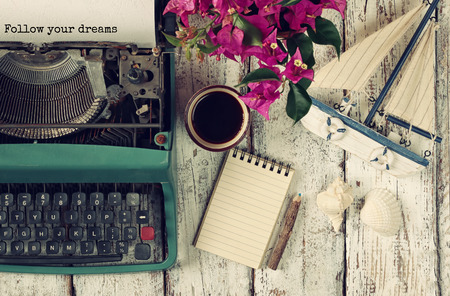 image of vintage typewriter with phrase Follow your dreams, blank notebook, cup of coffee and old sailboat on wooden table Stock Photo