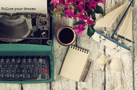 """secretaria: imagen de la máquina de escribir de la vendimia con la frase """"Sigue tus sueños"""", cuaderno en blanco, una taza de café y el viejo velero en mesa de madera"""