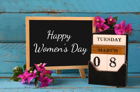 Drewniana 08 marca kalendarza, obok purpurowe kwiaty na starym niebieskim tamtejsze tabeli. selektywnej ostrości. rocznik filtrowane. Okazji koncepcji Międzynarodowy Dzień Kobiet