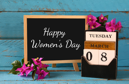 madera de marzo de 8 calendario, junto a flores de color púrpura en la vieja mesa rústica azul. atención selectiva. la vendimia se filtró. concepto Feliz Día Internacional de la Mujer
