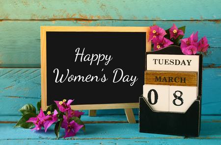 mujeres elegantes: madera de marzo de 8 calendario, junto a flores de color púrpura en la vieja mesa rústica azul. atención selectiva. la vendimia se filtró. concepto Feliz Día Internacional de la Mujer