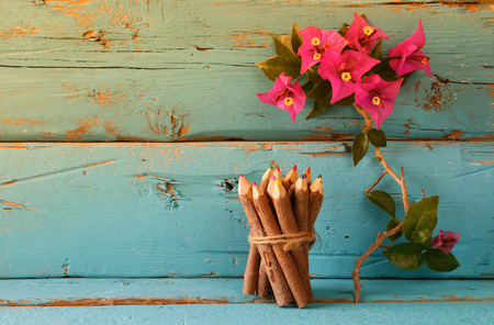 book concept: stack of wooden colorful pencils on wooden texture table next to purple bougainvillea flower