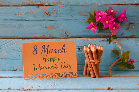 calendar day: vintage card with phrase: 8 march happy womens day on wooden texture table next to purple bougainvillea flower.