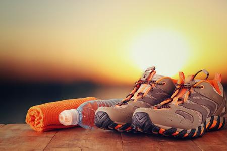ginástica: conceito da aptidão com o calçado desportivo, toalha e garrafa de água sobre a mesa de madeira na frente do pôr do sol paisagem.