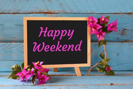 phrase: blackboard over blue wooden shelf with the phrase happy weekend Stock Photo