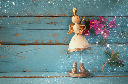 room decor: image of cute fairy princess on wooden table. vintage filtered with glitter overlay Stock Photo