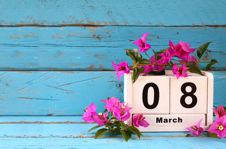 8 march: wooden March 8 calendar, next to purple flowers on old blue rustic table. selective focus. vintage filtered Stock Photo