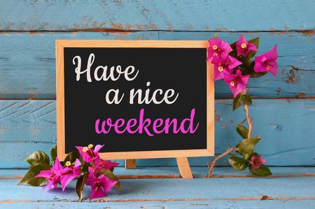fin de semana: pizarra sobre el estante de madera de color azul con la frase tenga un buen fin de semana