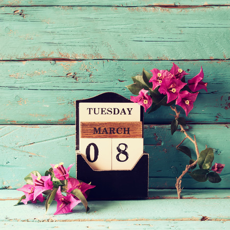 mar: wooden March 8 calendar, next to purple flowers on old blue rustic table. selective focus. vintage filtered Stock Photo
