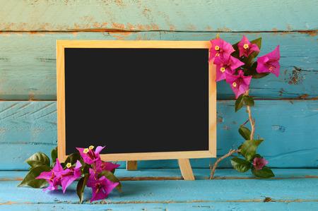 blank space: blank blackboard next to beautiful purple mediterranean summer flowers. vintage filtered. copy space