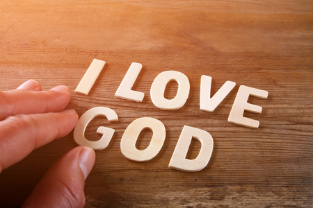 love image: man hand spelling the word i love god from wooden letters, retro style image