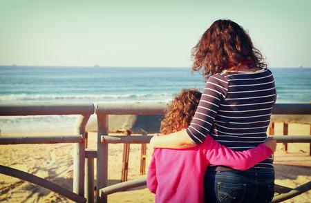 mujer mirando el horizonte: Imagen de la visión trasera de la madre y el niño mirando hacia delante en el mar. filtro de estilo retro Foto de archivo