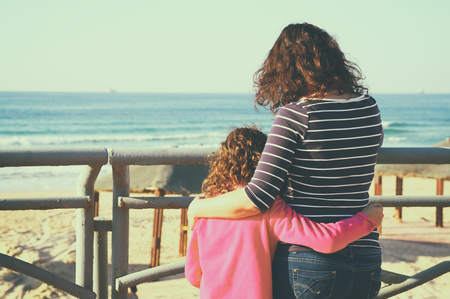familia abrazo: back view image of mother and child looking forward at the sea. retro style filter