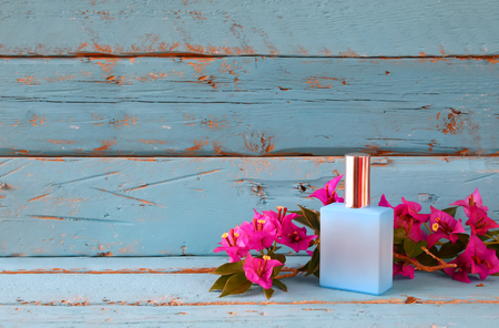 vintage perfume bottle next to bougainvillea flowers on wooden table