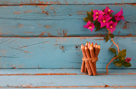 purple flower: stack of wooden colorful pencils on wooden texture table next to purple bougainvillea flower