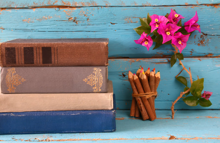 comprehension: stack of old books next to colorful pencils and bougainvillea flower on wooden table